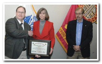 Dr. Richard Armstrong, deputy to the commander for training at the Ordnance School, presents a certificate of appreciation to Allison Guth, director of finance, National Institute for Automotive Excellence, during the opening moments of a business meeting Wednesday on the Ordnance Campus.